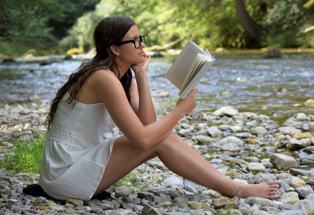 woman in nature reading sustainable lifestyle book