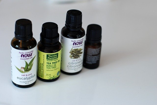 4 essential oil bottles on white table